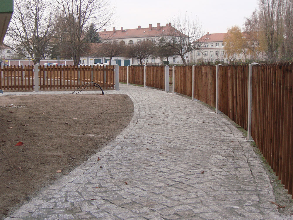 Erschließungsweg aus Natursteinpflaster, der durch eine mit Holzzäunen abgetrennte Gartenanlage führt