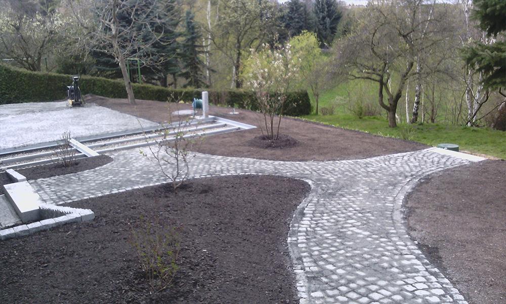 Gehölzflächen und gepflasterte Wege in einem Privatgarten in Dresden-Bannewitz, 2015