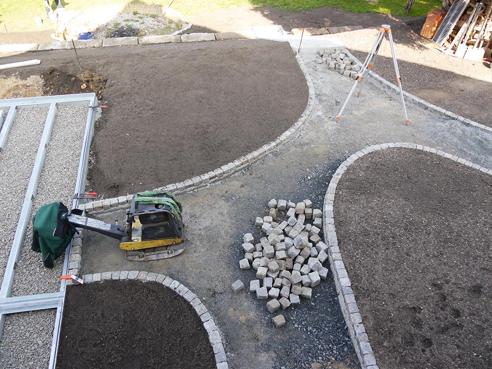 Anlegen eines Weges aus Natursteinpflaster in geschwungenen Bögen während der Bauphase