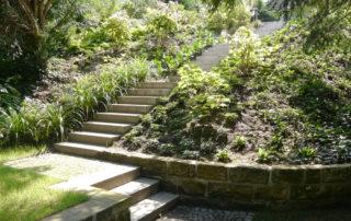 Blick vom unteren Gartenraum auf einen bepflanzten Hang mit einer Treppenanlage