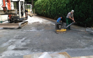 Verdichtung der Tragschicht mithilfe einer Rüttelplatte im Zuge des Wegebaus